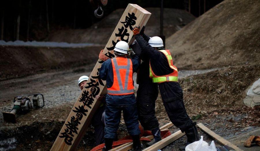 Des ouvriers installent un panneau de bois en hommage aux victimes du tremblement de terre et du tsunami dans un cimetière de la ville Kamaishi, dans la préfecture d'Iwate.