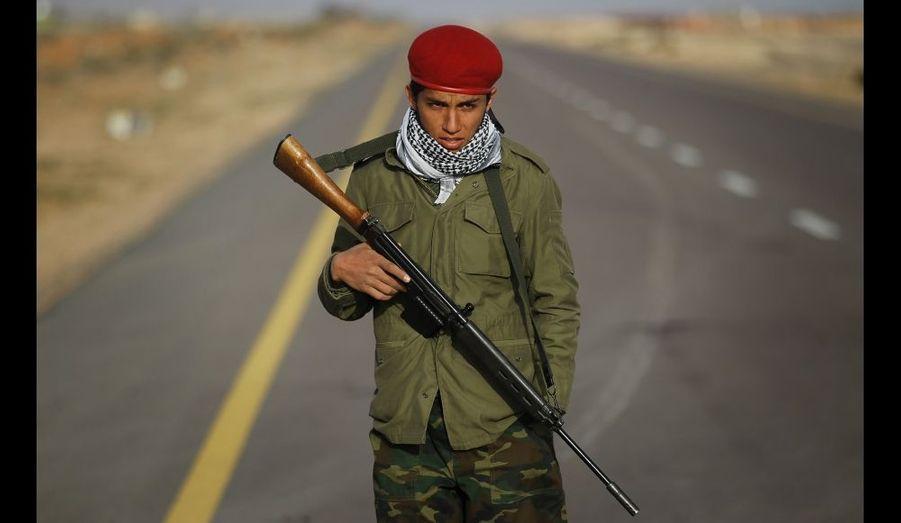 Un jeune combattant rebelle garde le denier point de contrôle de la route entre Bin Jawad et Nawfiliyah, où les forces fidèles à Mouammar Kadhafi ont mis fin à une rapide avancée des rebelles à environ 100 km à l'est de Syrte, dans l'est de la Libye.