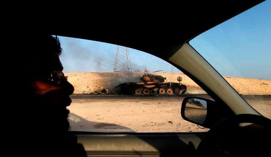 Les rebelles libyens ont considérablement progressé dans leur avancée vers Tripoli. Ici, un char de l'armée détruit fume encore au bord de la route qui mène à Syrte, le fief du colonel Kadhafi, qui semble en passe de tomber aux mains des rebelles.