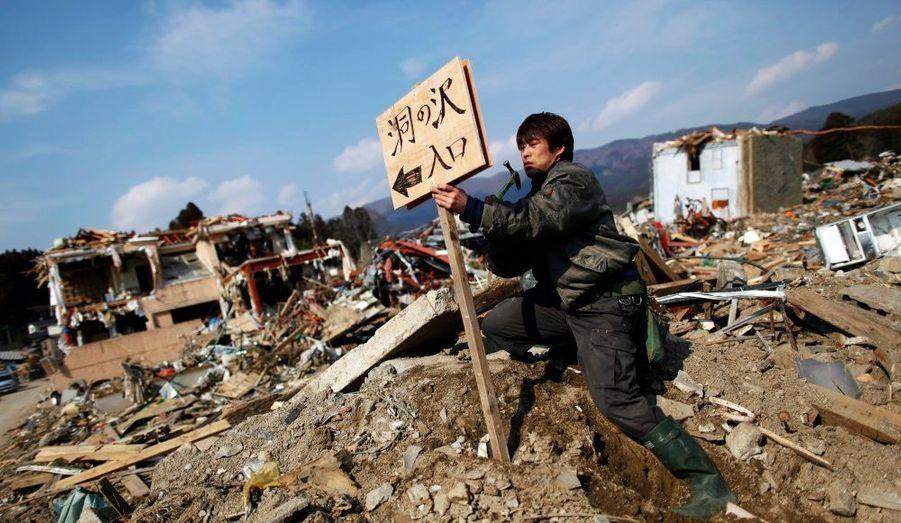 """Un homme installe une pancarte avec le nom de son quartier dévasté par le tsunami à Rikuzentakata, dans la préfecture d'Iwate. Il y est inscrit: """"Entrée d' Horanosawa""""."""