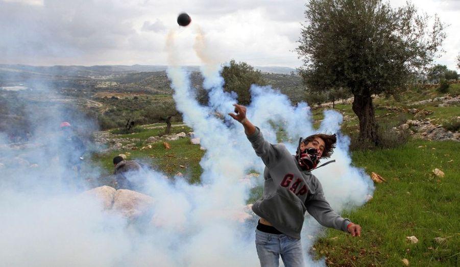 Un jeune Palestinien renvoie une grenade lacrymogène lancée par les forces israéliennes, lors d'une manifestation près de Ramallah, le 25 mars dernier.