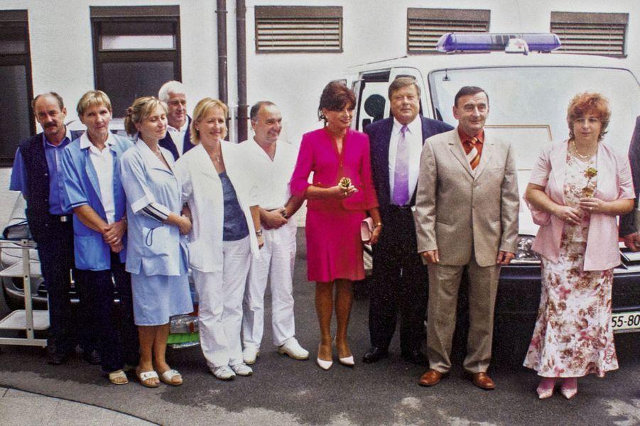 Amalija et Viktor Knauss (au centre), les parents de Melania, en 2006, devant le centre de santé, à Sevnica, auquel ils remettent une donation de 25 000 dollars de la part de leur fille.