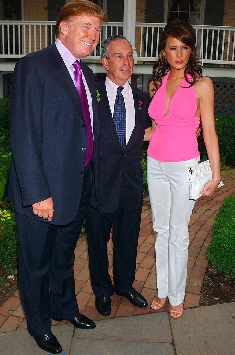 Donald Trump, Michael Bloomberg et Melania Knauss lors d'une réception organisée à l'occasion du passage de la torche olympique à New York, en juin 2004.