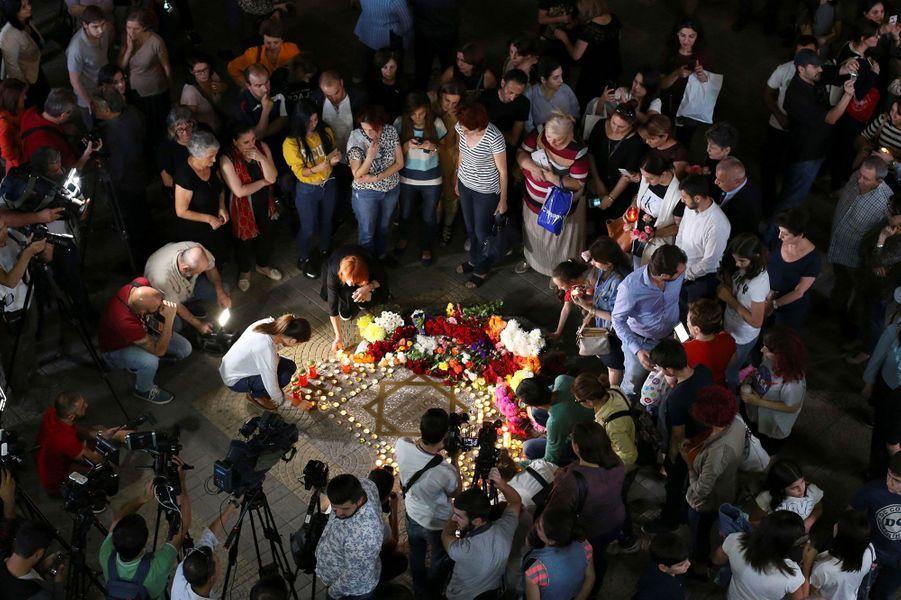 Des anonymes se recueillent sur la place Charles Aznavour, à Erevan, en Arménie
