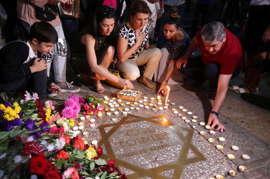 Des anonymes se recueillent sur la placeCharles Aznavour, àErevan, en Arménie