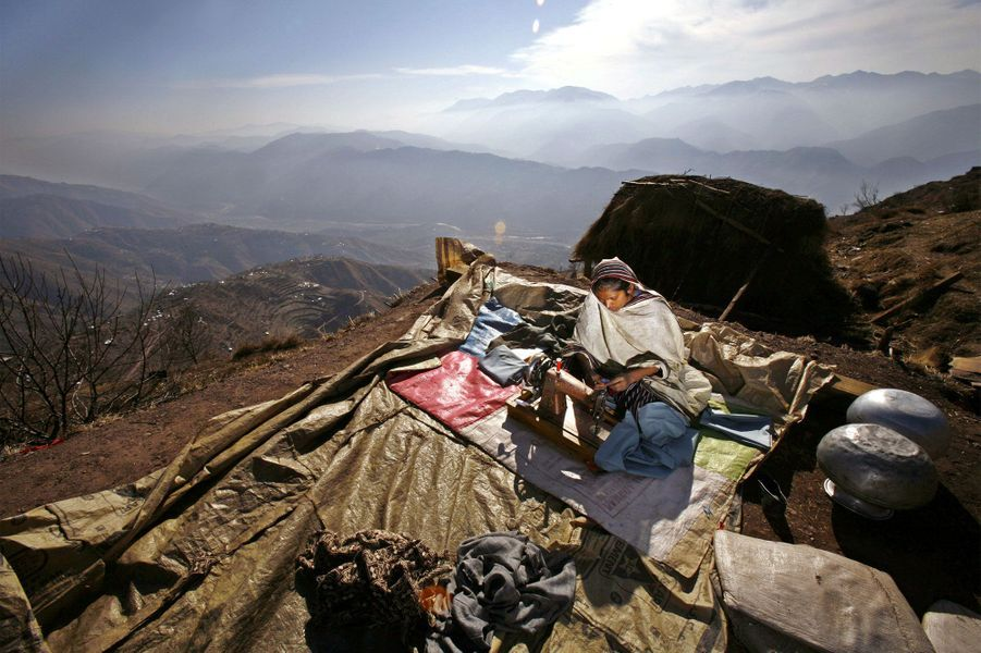2006, après le tremblement de terre qui a dévasté la région du Cachemire, une survivante fait de la couture en haut d'une montagne.