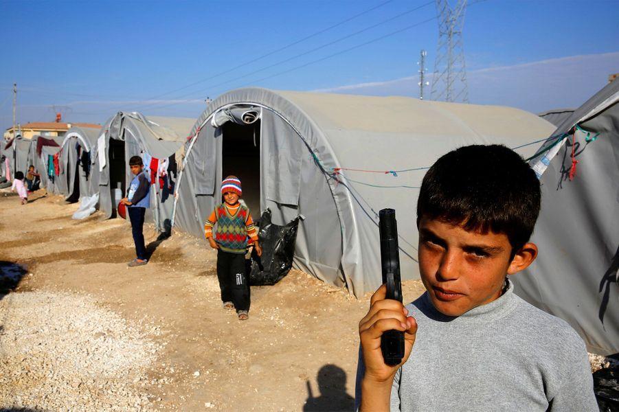27 octobre 2014, un petit réfugié kurde joue avec un faux pistolet dans un camp situé en Turquie.
