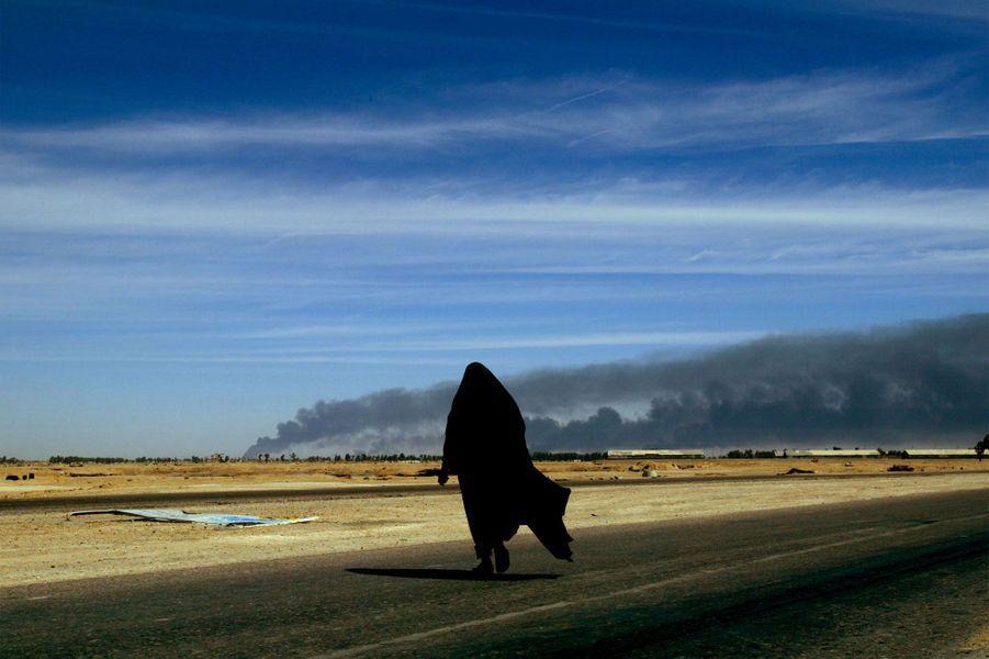 Le 3 avril 2003, une Irakienne rentre dans la ville de Bassorah, dans le sud du pays, alors que des incendies font rage.