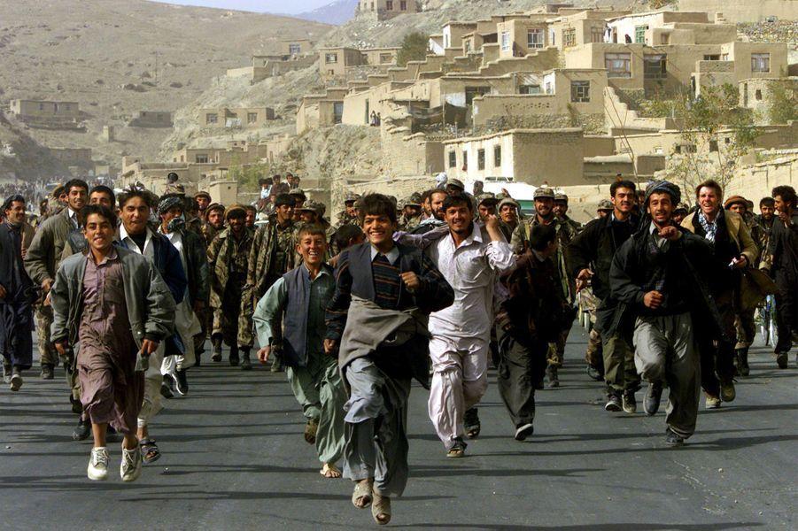 Les habitants de Kaboul célèbrent et escortent des combattants de l'Alliance du Nord qui entrent dans la capitale afghane, Kaboul, le 13 novembre 2001. Les forces de l'Alliance du Nord anti-talibans sont entrées à Kaboul, des informations faisant état de l'effondrement du pouvoir des talibans.