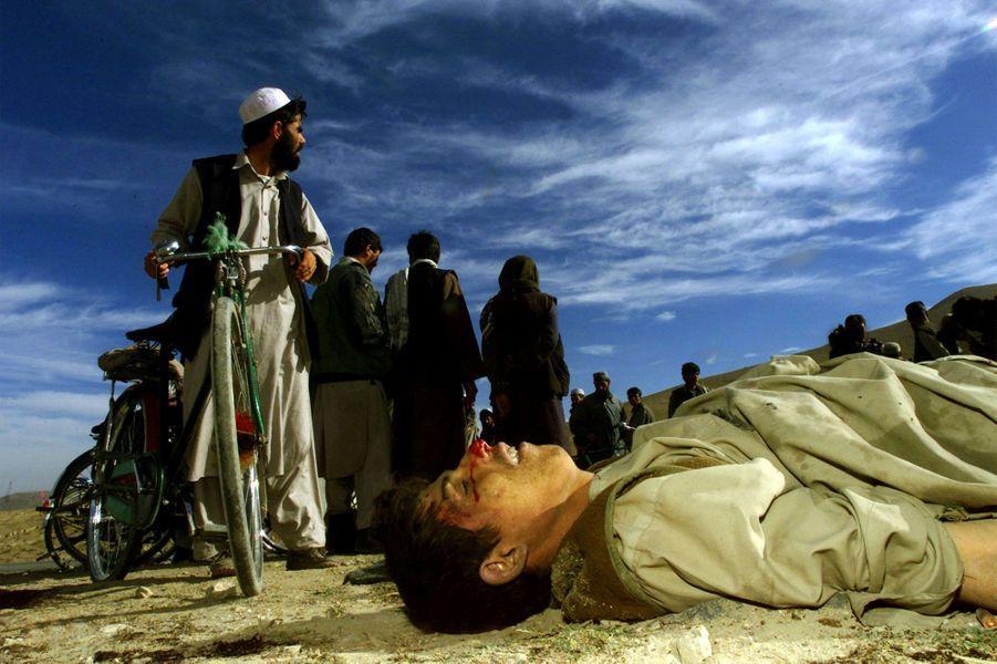 Des civils afghans observent des combattants talibans décédés tôt le matin sur l'autoroute, à trois kilomètres au nord de Kaboul, alors que des combattants de l'Alliance du Nord approchaient de Kaboul, la capitale afghane, le 13 novembre 2001.