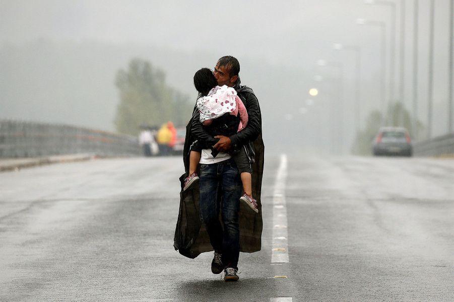 Un réfugié syrien embrasse sa fille, en 2015, alors qu'il marche à la frontière entre la Grèce et la Macédoine.