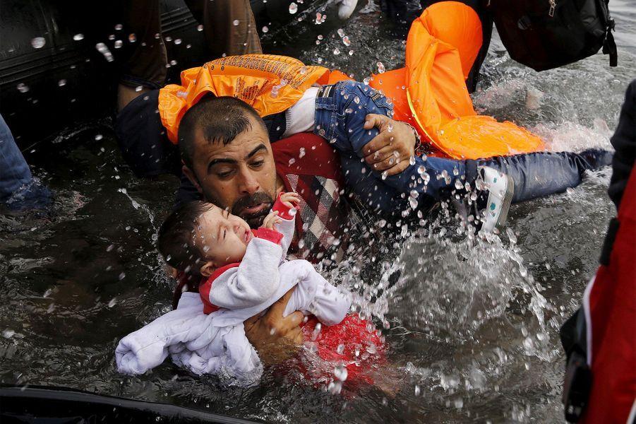 Un réfugié syrien s'accroche à ses enfants alors qu'il lutte pour sortir d'un dériveur sur l'île grecque de Lesbos, après avoir traversé une partie de la mer Égée de la Turquie à Lesbos le 24 septembre 2015.