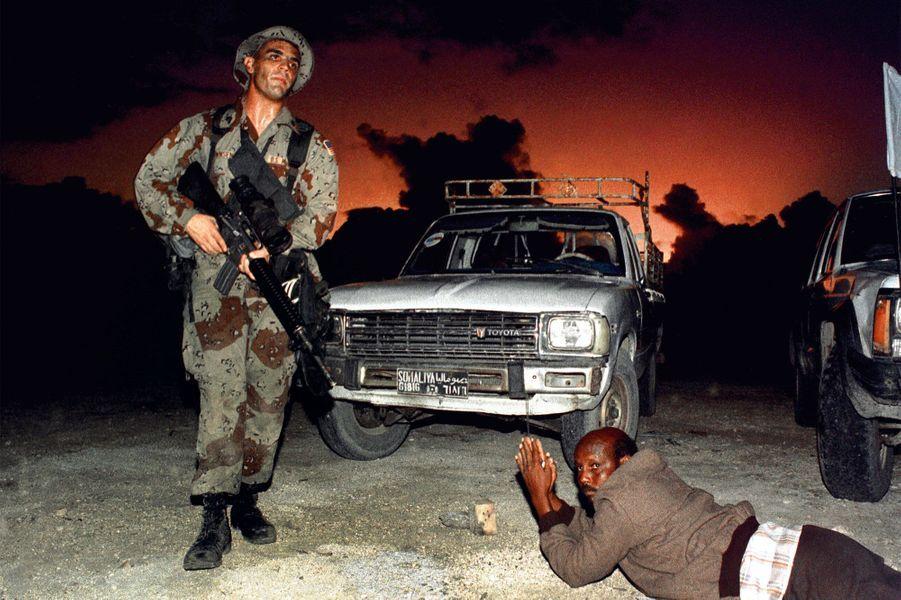 9 décembre 1992, un conducteur somalien est allongé au sol alors qu'un soldat américain sécurise la zonedans le port de Mogadiscio.