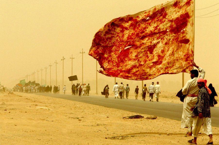 Un homme chiite irakien porte un drapeau taché du sang d'hommes qui se sont blessés pour manifester leur amour pour l'imam alors qu'il marchait avec des dizaines de milliers de religieux irakiens se dirigeant vers la ville centrale de Kerbala le 19 avril , 2003.