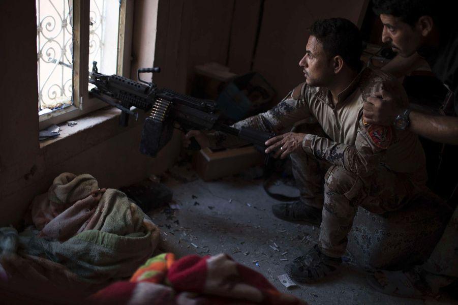 Dans un immeuble désaffecté, des soldats iraquiens observent les positions de l'ennemi près de la Grande mosquée al-Nouri.