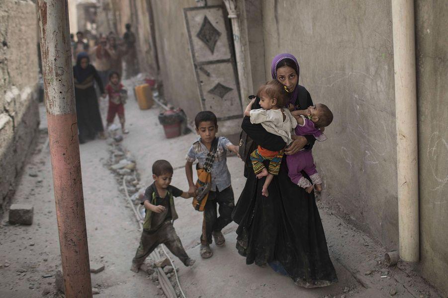 Au milieu de la vieille ville de Mossoul, en ruines, une mère tente de fuir avec ses enfants.