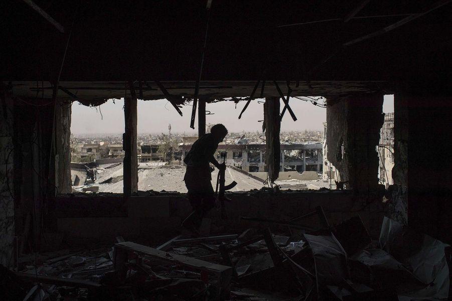 Un policier iraquien marche dans un immeuble qui était autrefois un ancien complexe hospitalier.