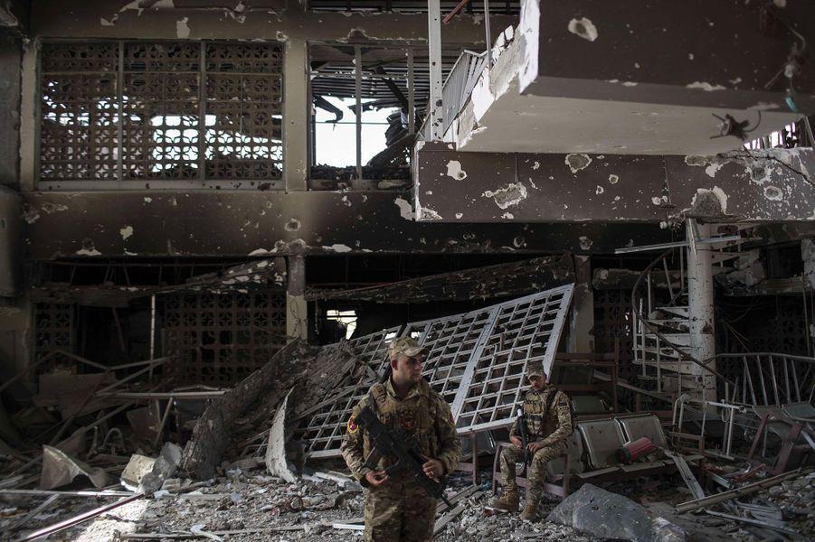 Deux policier iraquiens se tiennent dans ce qui était avant le conflit le plus grand hôpital de Mossoul.