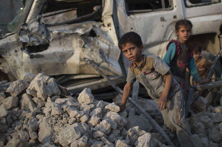 Deux enfants irakiens se tiennent dans les décombres.