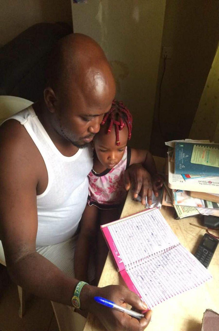 Obi C. Kingsley et sa fille, Special, en train d'écrire son téoignage à Benin City.