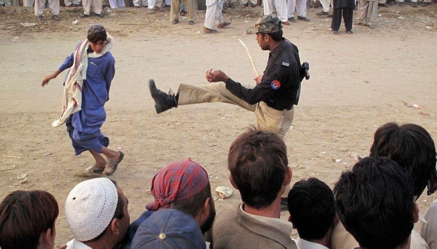 Un militaire pakistanais renvoie un enfant dans la queue à un point de ravitaillement pour les personnes déplacées en raison des combats au Sud Waziristan