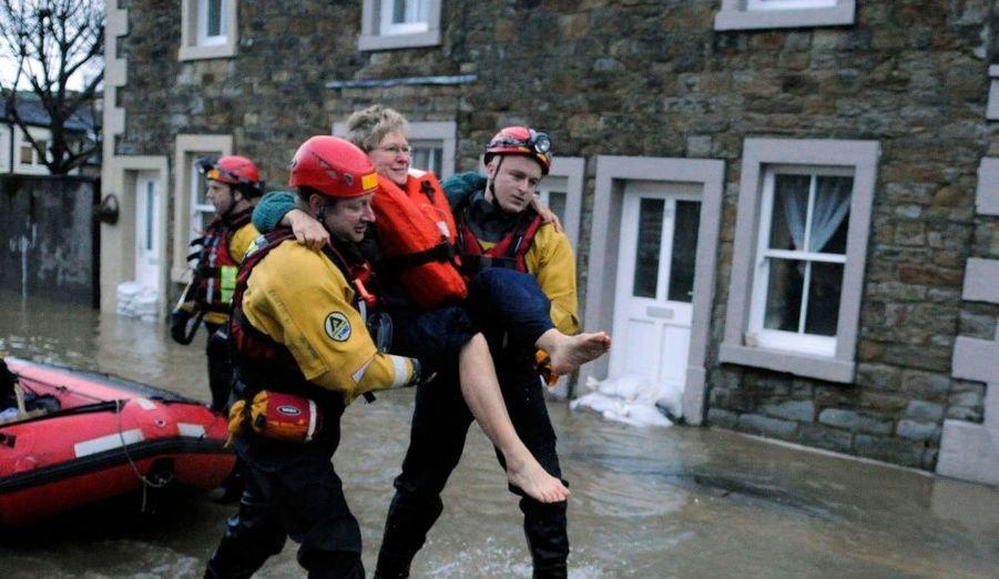 """De soudaines inondations ont emporté maisons et ponts au nord de l'Angleterre dans la nuit de jeudi à vendredi, obligeant à l'évacuation de centaines de personnes par hélicoptère et par bateaux. Un policier est porté disparu et des dizaines d'habitations restent inaccessibles. Certains sinistrés se sont d'ailleurs réfugiés sur le toit de leur maison. """"C'est un sinistre extrêmement grave. Nous avons subi des pluies sans précédent"""", a expliqué le président de l'Agence pour l'environnement Chris Smith en précisant que 314 mm de pluies sont tombées en 24 heures. Selon l'Office météorologique national, il s'agit-là de l'équivalent des précipitations moyennes pour un mois de novembre dans la région, soit un record absolu pour la Grande-Bretagne."""