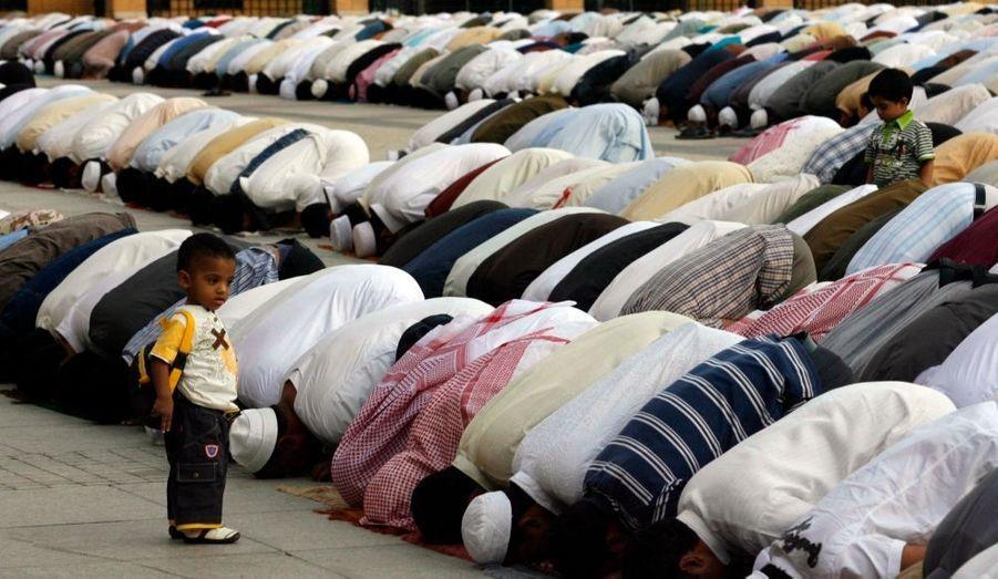Un enfant observe des fidèles faire leur prière à Riyad en Arabie Saoudite. Les musulmans célèbrent aujourd'hui le premier jour de l'Aïd al-Adha. Cette fête commémore le souvenir d'Ibrahim qui a failli immoler son fils Ismaïl avant que l'ange Gabriel ne lui propose au dernier moment de sacrifier un mouton à sa place.