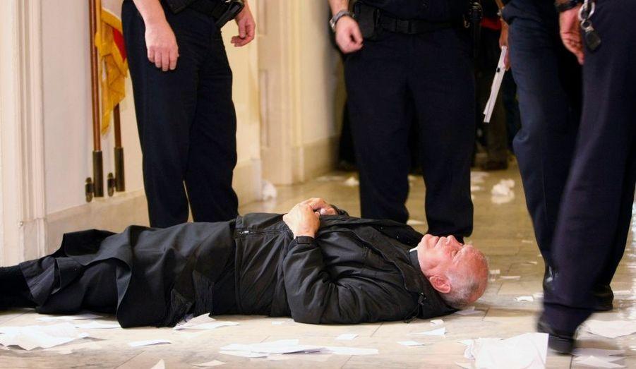 Un prêtre allongé par terre proteste contre la réforme de santé proposée par Barack Obama, ici dans le bureau de Nancy Pelosi, au Capitol à Washington.