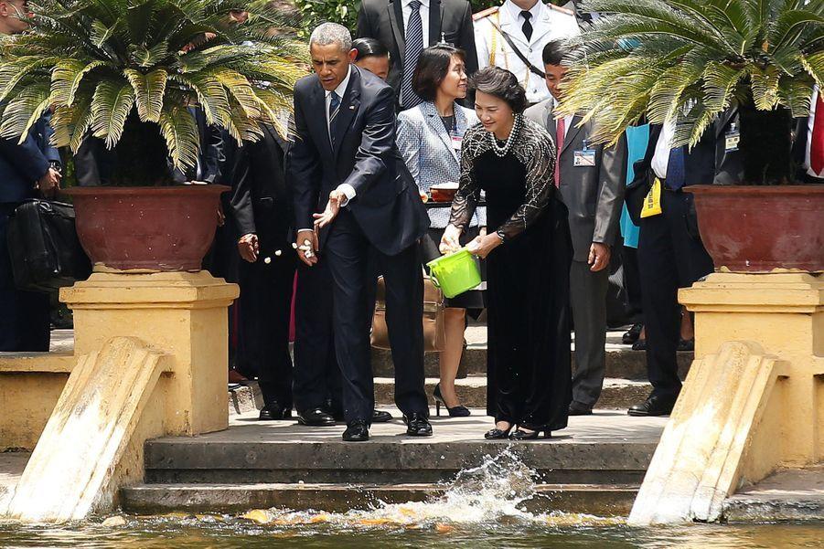 Barack Obama et la présidente de l'Assemblée nationale Nguyen Thi Kim Ngan nourissant des poissons dans les jardins présidentiels