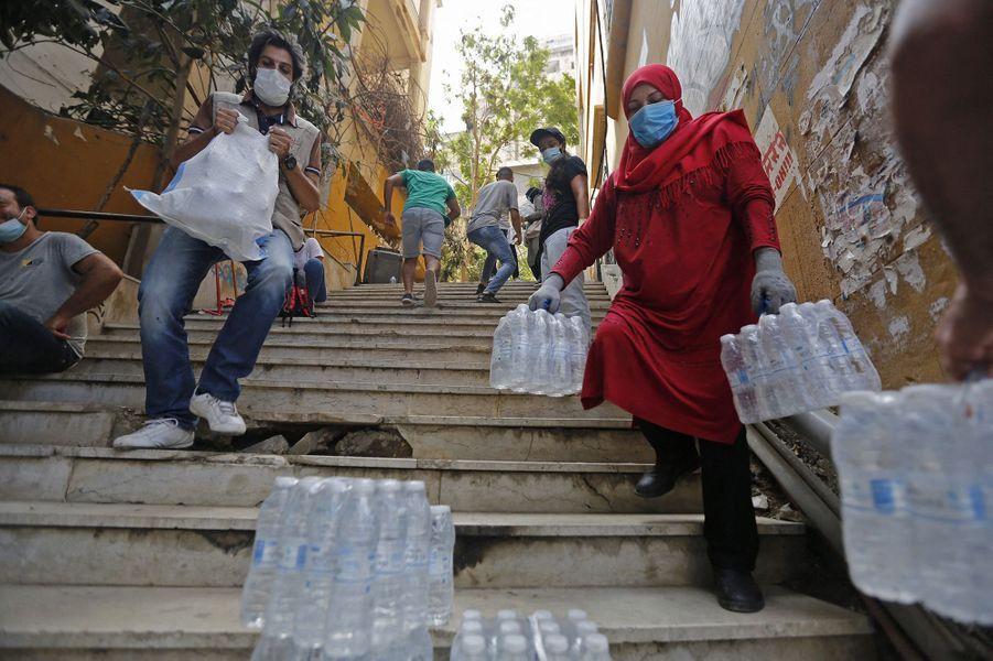 Des bénévoles distribuent des bouteilles d'eau et des produits de première nécessité à Beyrouth, trois jours après les explosions qui ont fait plus de 150 morts, le 7 août 2020