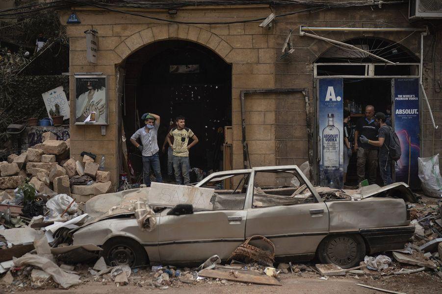 Des personnes se tiennent dans le centre de Beyrouth au milieu des gravats, trois jours après les explosions qui ont fait plus de 150 morts, le 7 août 2020