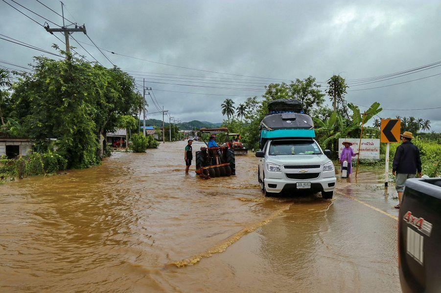 Des personnes tentent d'avancer sur une route inondée dans la province de Loei en Thaïlande le 2 août 2020