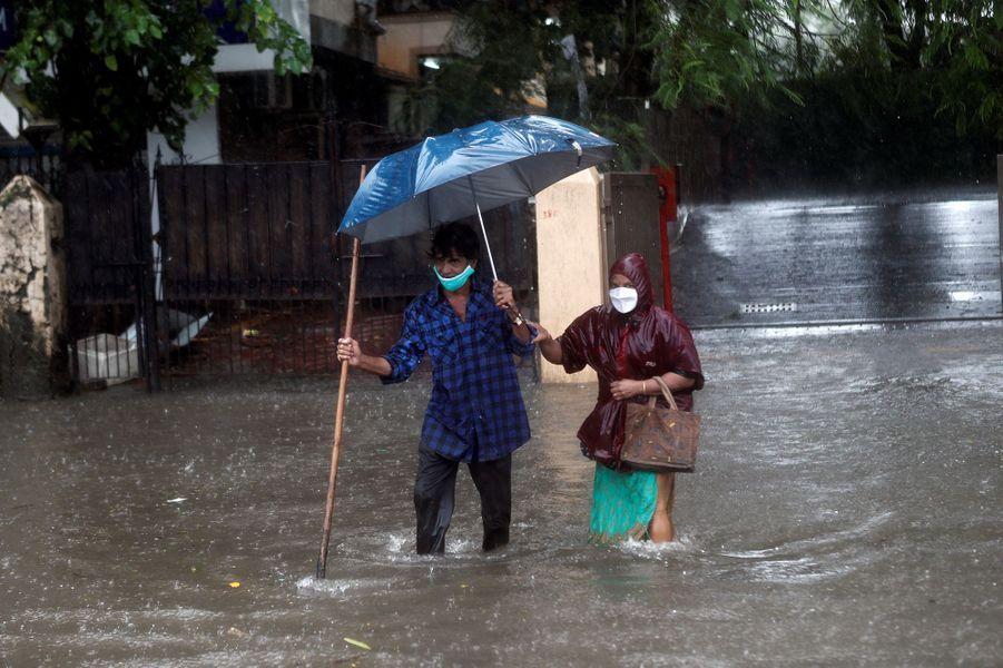 Un homme et une femme traversent une route inondée à Mumbai en Inde le 5 août 2020