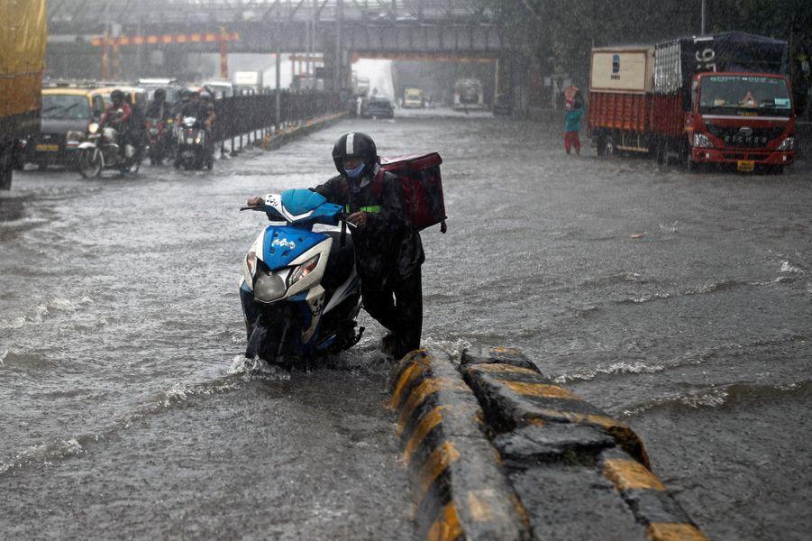 Un coursier pousse son scooter dans une route inondée de Mumbai en Inde le 5 août 2020