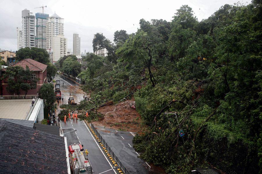 Des pompiers en intervention sur une route après des inondations et un glissement de terrain à Mumbai en Inde le 6 août 2020