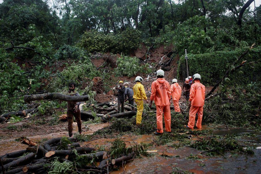 Des pompiers et des bénévoles constatent les dégâts après un glissement de terrain provoqué par des inondations à Mumbai en Inde le 6 août 2020