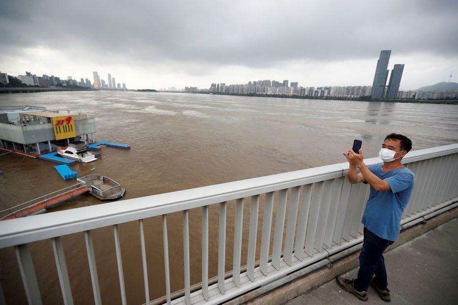 Un homme prend une photo au-dessus du fleuve Han à Séoul en Corée du Sud après des inondations le 6 août 2020