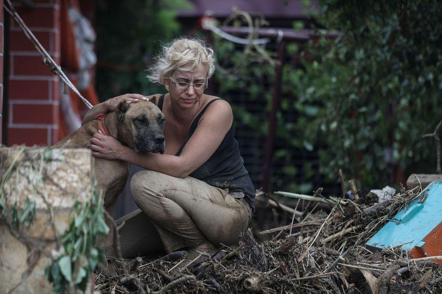 Une femme et son chien sur l'île d'Eubée après des inondations le 9 août 2020
