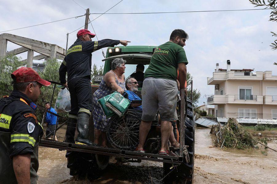 Des pompiers et des habitants évacuent des résidents sur l'île d'Eubée en Grèce après des inondations le 9 août 2020