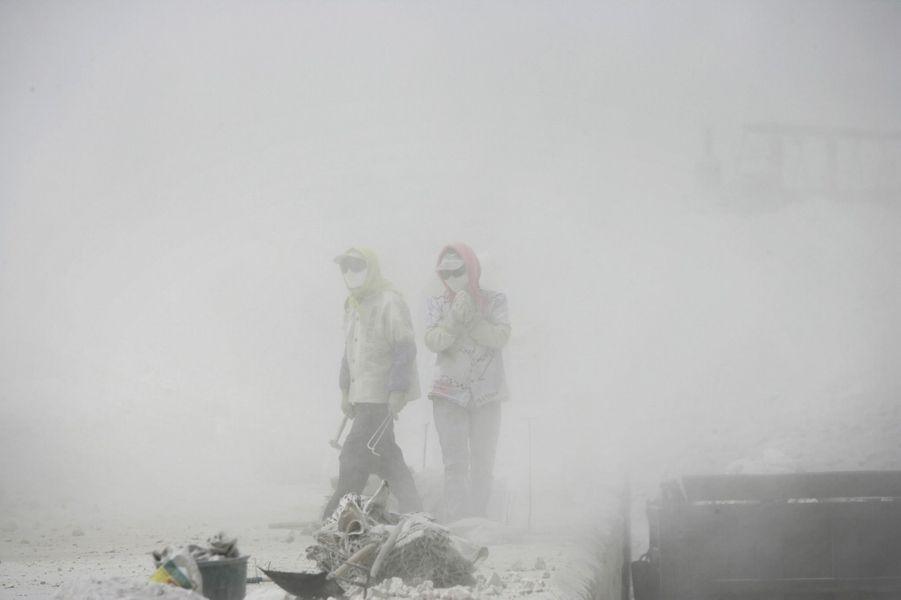 Des ouvriers dans le brouillard empoisonné de Wuhai, en Mongolie-Intérieure. La ville aux 400usines est la plus polluée de Chine. Aux alentours, tous les arbres sont calcinés.