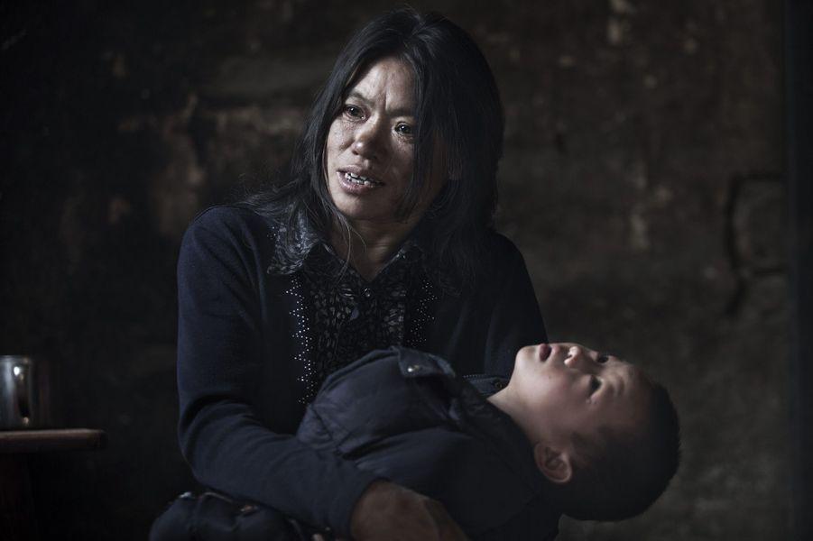 Li Xu, 3ans, dans les bras de sa grand-mère. L'hôpital a relevé un taux excessif de plomb dans son sang.