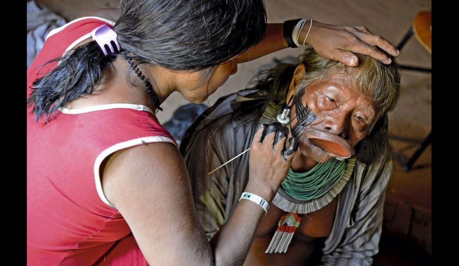 Séance de maquillage avec une de ses filles. Cette peinture noire, à base de cendres et de baie jenipapo, tient dix jours.