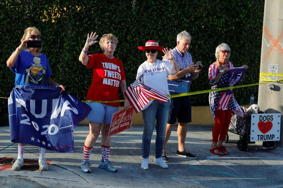Opposants et partisans de Donald Trump ont manifesté le long de la route empruntée pour se rendre à l'aéroport de Palm Beach, le 1er décembre 2019.