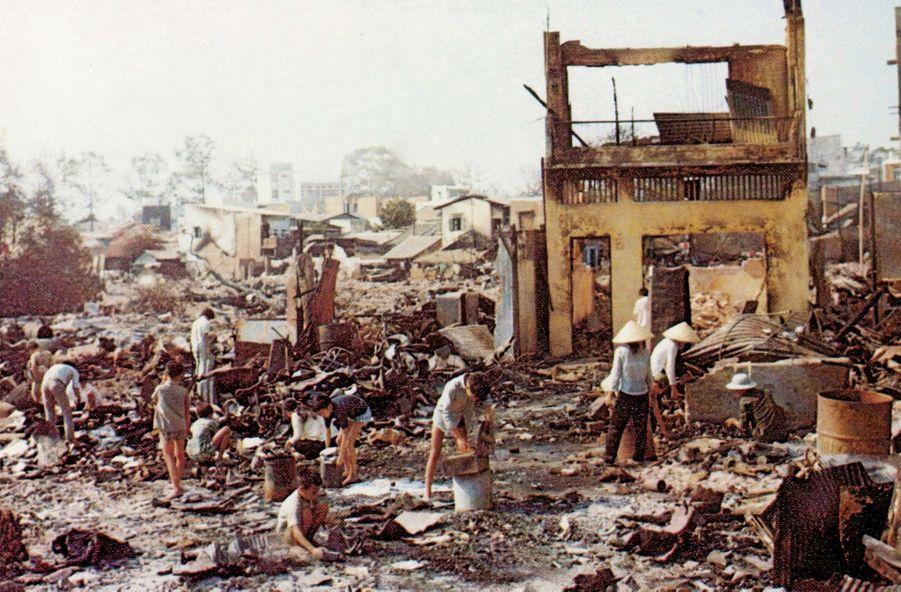 Des civils errent dans les rues détruites de Saigon.
