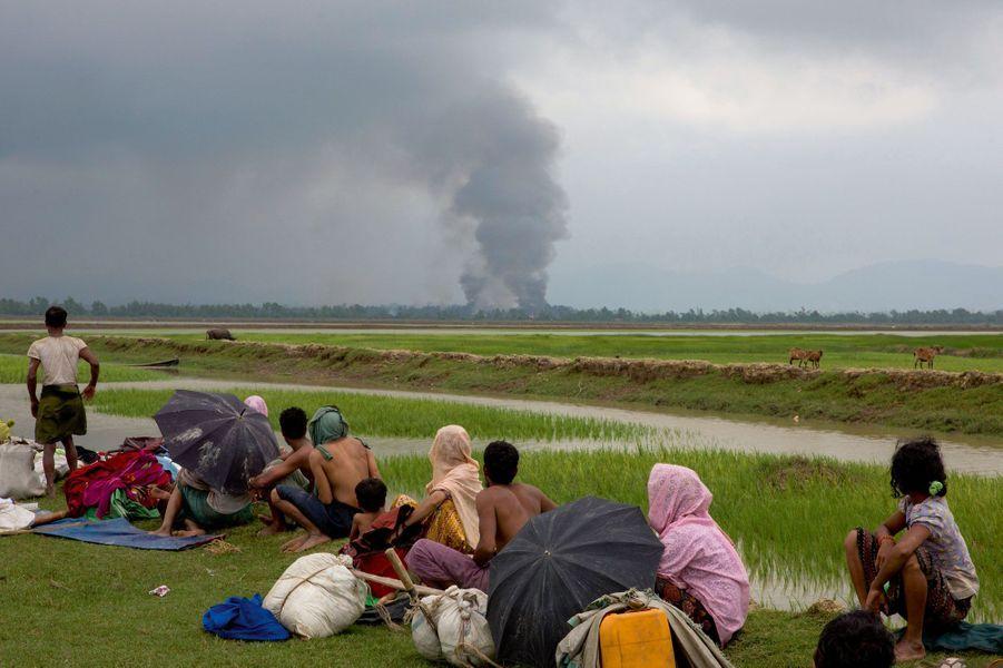 En pleine mousson, sur des routes boueuses, des villageois s'enfuient tandis que leurs maisons brûlent. Dans le Bangladesh voisin,surpeuplé et misérable,les bidonvilles se multiplientà la frontière.