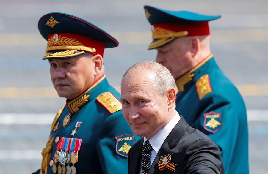 Vladimir Poutine quitte les cérémonies accompagné de son ministre de la défense Sergei Shoigu et du chef des opérations armées de la RussieOleg Salyukov.