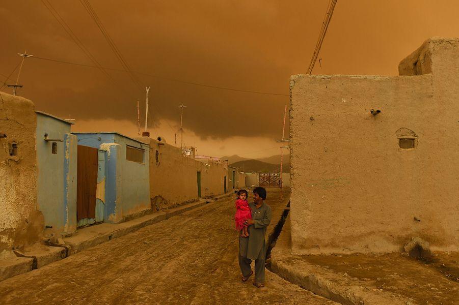 19 avril 2015, un père transporte sa fille alors qu'il pleut à Kaboul.