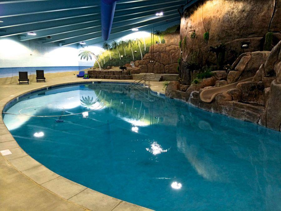 La piscine avec cascades et décor de faux palmiers.