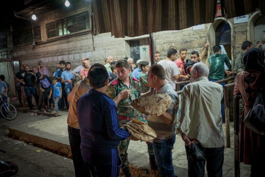 Distribution de pain encadrée par l'armée loyaliste. Son prix est passé de 70 cents à 1 dollar en quelques jours.