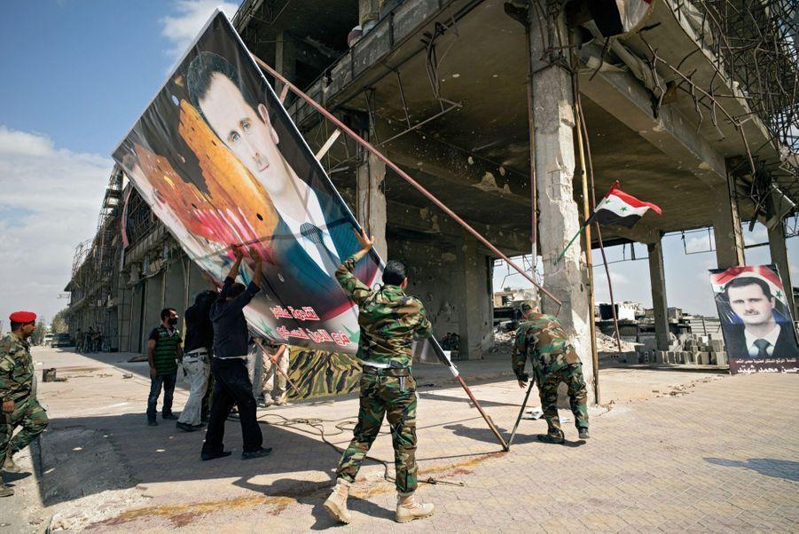 Le 22 septembre, Ramouseh, quartier sud de la ville. Les militaires gouvernementaux dressent un portrait de leur président.